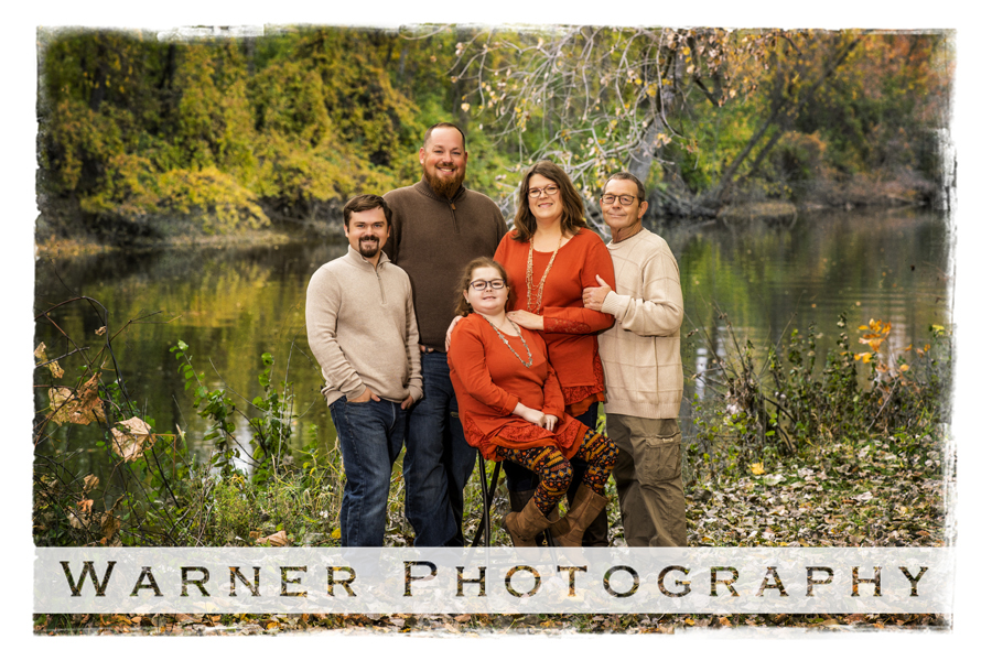outdoor family portrait of the Plummer family by the water at Chippewa Nature Center
