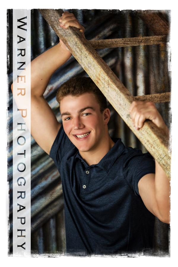 studio portrait of Frankenmuth High School senior Travis on a metal wall with a wooden ladder