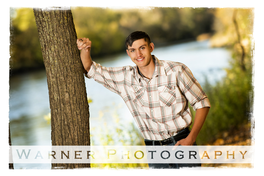 outdoor senior portrait of Bay City Wester senior Tyler at Chippewa Nature Center by the water and a tree