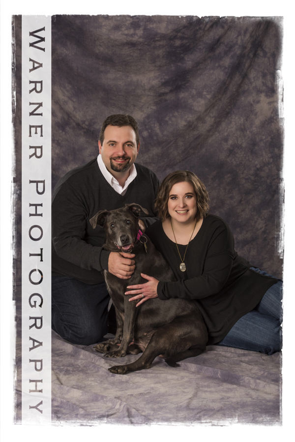 Studio portrait of the Banker family and their dog Pheonix a chocolate lab