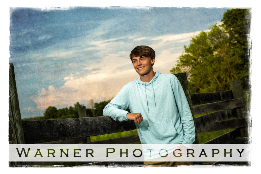 Outdoor portrait of Dow High School senior Adam at Chippewa nature Center by a wooden fence and the sunset