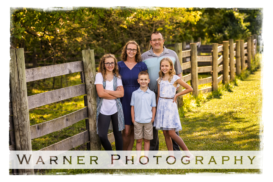 Outdoor family portrait of the Frazee family at Chippewa Nature Center with a wooden fence