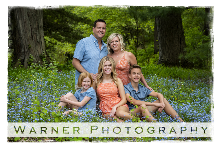 an outdoor portrait of the Buckhave family at dow gardens with small blue flowers