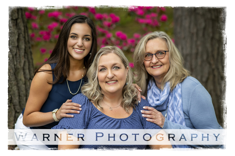 an outdoor family portrait of the Luebkert family at Dow Gardens with pink flowers