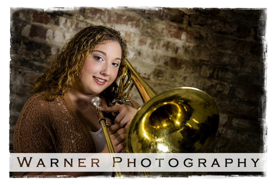 a studio portrait of Clare High School senior Amaris with her trombone